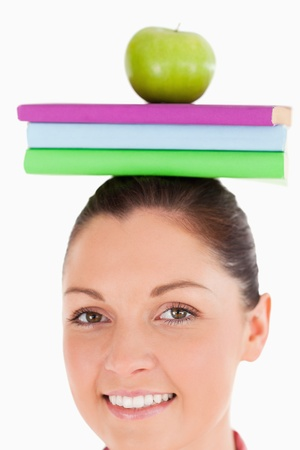 Beautiful female holding an apple and books on her head while standing against a white background photo