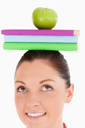 Attractive female holding an apple and books on her head while standing against a white background photo