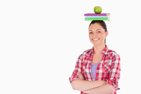 Pretty female holding an apple and books on her head while standing against a white background photo