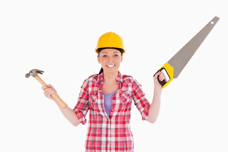 Pretty woman holding a saw and a hammer while standing against a white background photo