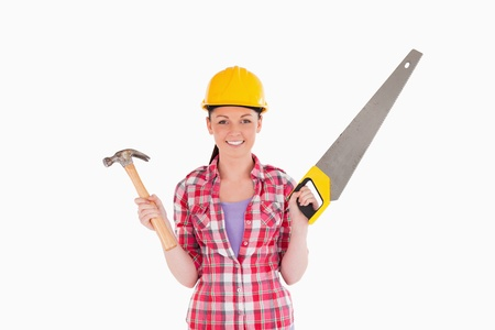 Attractive woman holding a saw and a hammer while standing against a white background photo