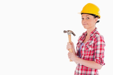 Beautiful woman holding a hammer while standing against a white background photo