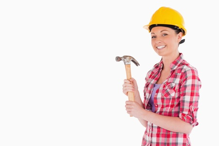 Attractive woman holding a hammer while standing against a white background photo