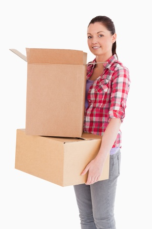 carboard box: Attractive woman holding cardboard boxes while standing against a white background