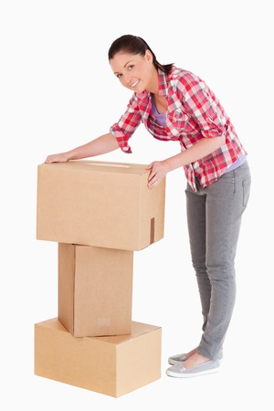carboard box: Good looking woman posing with cardboard boxes while standing against a white background
