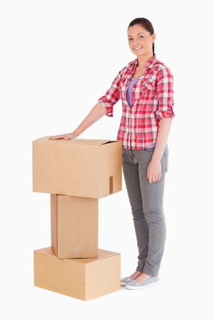 carboard box: Beautiful woman posing with cardboard boxes while standing against a white background