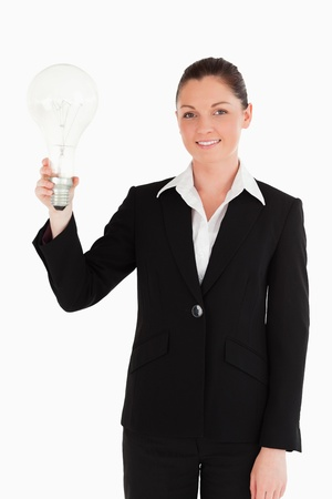Lovely woman in suit holding a light bulb while standing against a white background photo
