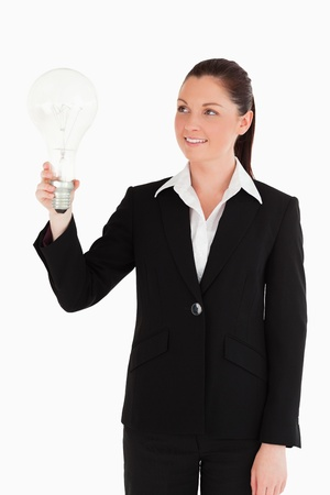 Beautiful woman in suit holding a light bulb while standing against a white background photo