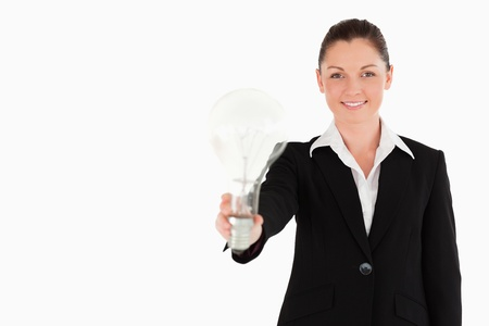 Attractive woman in suit holding a light bulb while standing against a white background photo
