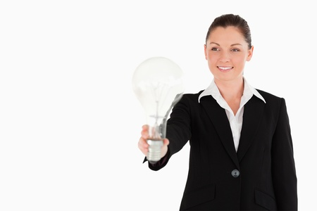 Charming woman in suit holding a light bulb while standing against a white background photo