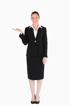 Gorgeous woman in suit showing a copy space while standing against a white background Stock Photo - 11179218