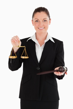 Good looking woman in suit holding scales of justice and a gavel while standing against a white background photo