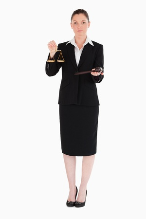 Charming woman in suit holding scales of justice and a gavel while standing against a white background photo