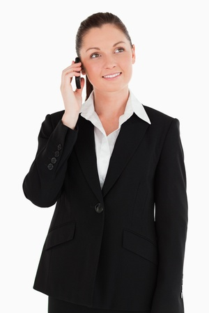 Gorgeous woman in suit on the phone while standing against a white background photo