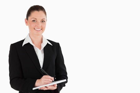 Portrait of a good looking woman in suit writing on a notebook while standing against a white background photo