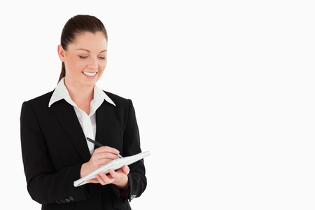 Portrait of a charming woman in suit writing on a notebook while standing against a white background photo