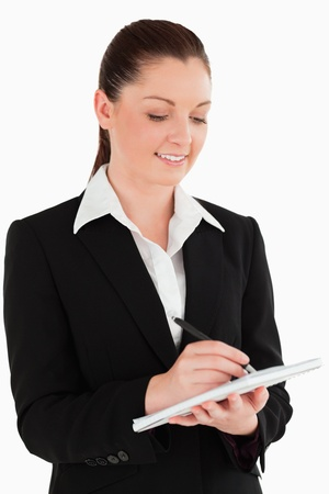 Portrait of a gorgeous woman in suit writing on a notebook while standing against a white background photo
