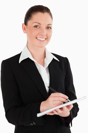 Portrait of a cute woman in suit writing on a notebook while standing against a white background photo