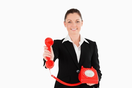 Charming woman in suit holding a red telephone while standing against a white background photo