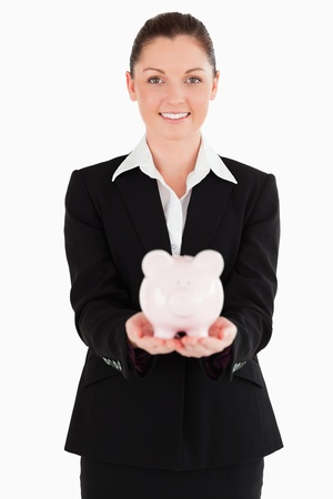 Attractive woman in suit holding a pink piggy bank while standing against a white background photo