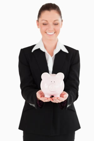 Good looking woman in suit holding a pink piggy bank while standing against a white background photo