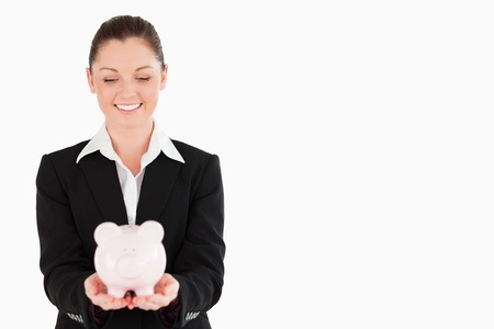 Gorgeous woman in suit holding a pink piggy bank while standing against a white background photo