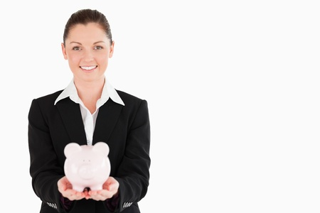 Charming woman in suit holding a pink piggy bank while standing against a white background photo