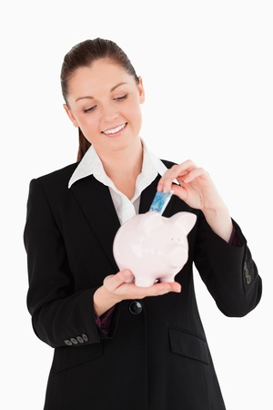 Beautiful woman in suit inserting a money bill in a pink piggy bank while standing against a white background photo