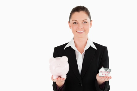 Beautiful woman in suit holding a piggy bank and a miniature house while standing against a white background photo