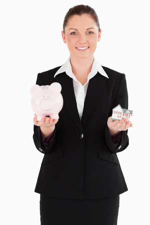 Attractive woman in suit holding a piggy bank and a miniature house while standing against a white background photo