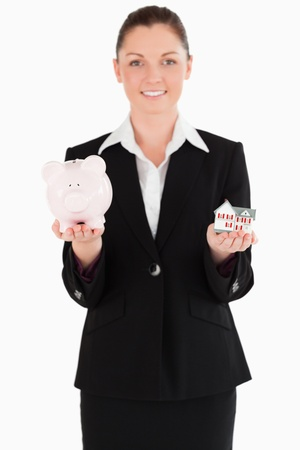 Good looking woman in suit holding a piggy bank and a miniature house while standing against a white background photo