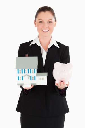 Pretty woman in suit holding a piggy bank and a miniature house while standing against a white background photo