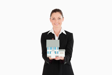 Pretty woman in suit holding a miniature house while standing against a white background photo