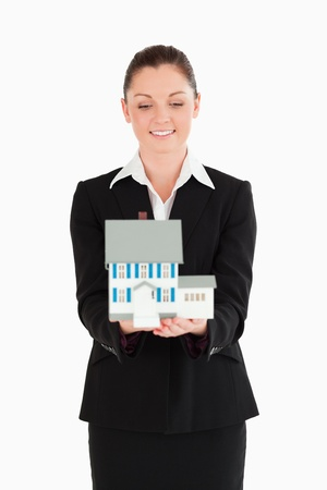 Beautiful woman in suit holding a miniature house while standing against a white background photo