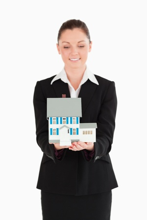 Attractive woman in suit holding a miniature house while standing against a white background photo