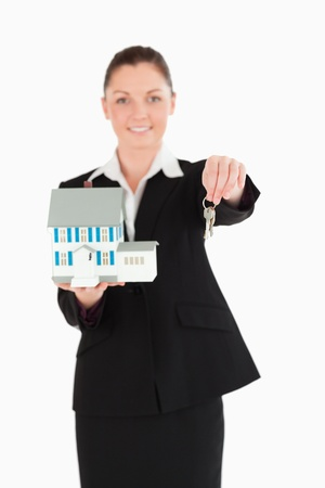 Pretty woman in suit holding keys and a miniature house while standing against a white background photo