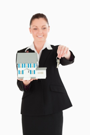 Beautiful woman in suit holding keys and a miniature house while standing against a white background photo