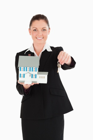 Attractive woman in suit holding keys and a miniature house while standing against a white background photo