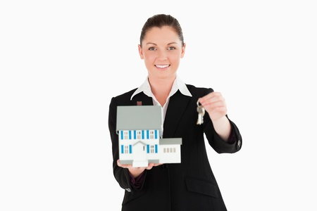 Good looking woman in suit holding keys and a miniature house while standing against a white background photo
