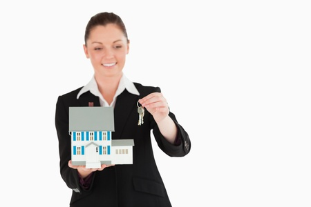 Charming woman in suit holding keys and a miniature house while standing against a white background photo