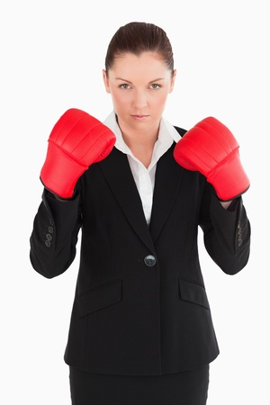 Charming woman wearing some boxing gloves while standing against a white background photo