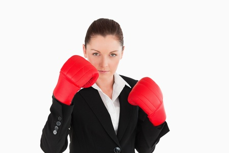 Beautiful woman wearing some boxing gloves while standing against a white background photo