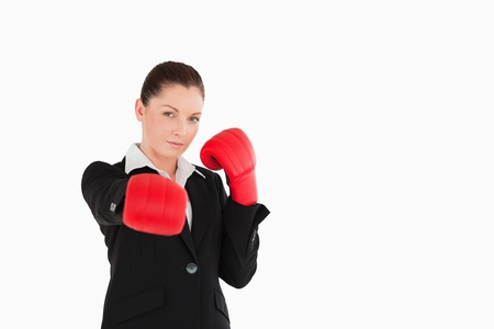 Good looking woman wearing some boxing gloves while standing against a white background photo