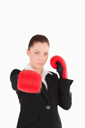 Cute woman wearing some boxing gloves while standing against a white background Stock Photo - 11180608