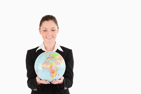 Good looking woman in suit holding a globe while standing against a white background photo