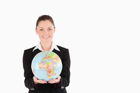 Charming woman in suit holding a globe while standing against a white background Stock Photo - 11179287