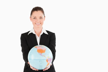 Gorgeous woman in suit holding a globe while standing against a white background photo