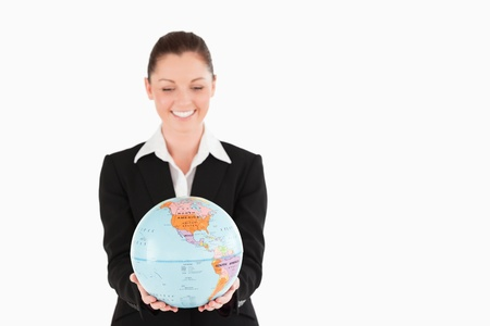 Lovely woman in suit holding a globe while standing against a white background Stock Photo - 11179340