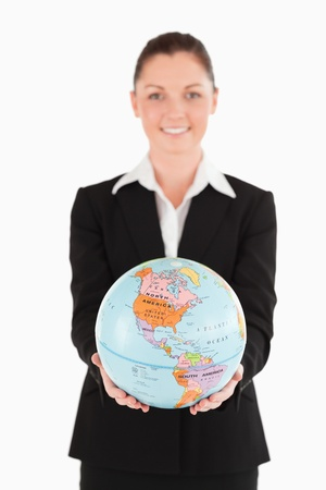 Good looking female in suit holding a globe while standing against a white background photo