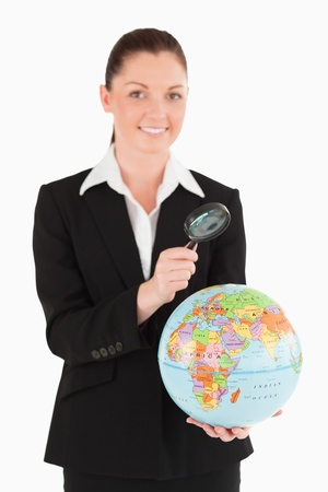 Attractive female in suit holding a globe and using a magnifying glass while standing against a white background Stock Photo - 11191662